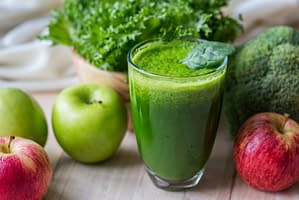 glass of green juice with apples and vegetables around it