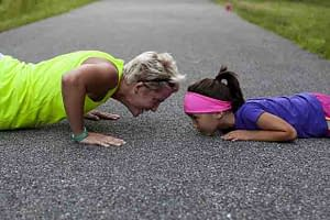 woman and child doing push ups outside