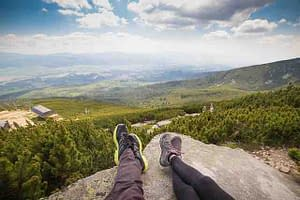 man and woman's feet on a rock overlooking a valley