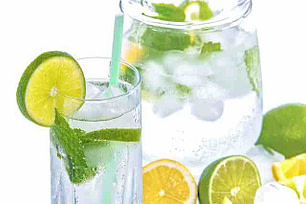 glass and pitcher of water with limes and lemons