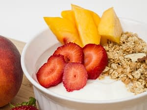 bowl of yogurt with fruit and granola on top