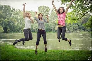 3 girls jumping by a pond smiling