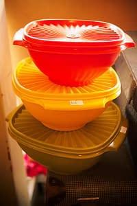 three tupperware bowls red orange and yellow