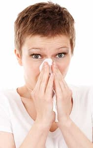 woman with tissue sneezing