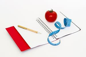 journal with pencil apple and tapemeasure