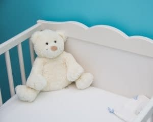 crib with white teddy bear and blue room