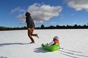 woman in snow with child in sled