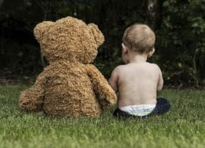 baby with teddy bear on grass
