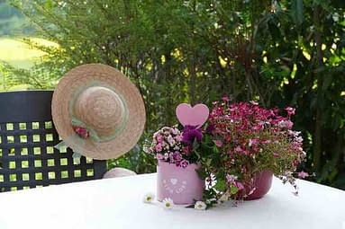 Two vases of flowers, a sunhat hanging over a chair with a table in a garden