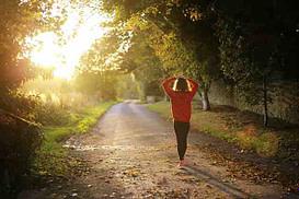 women walking down a dirt path with fall foliage