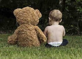 toddler sitting on a lawn with a large teddy bear