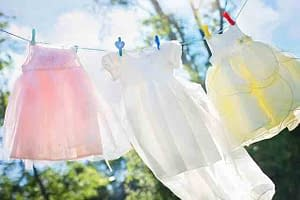 little girls dresses hanging on a clothes line in the sun