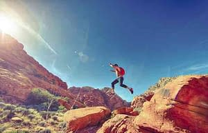 man jumping red rocks sunshine happy energetic