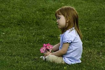 little girl holding flowers sitting on a lawn